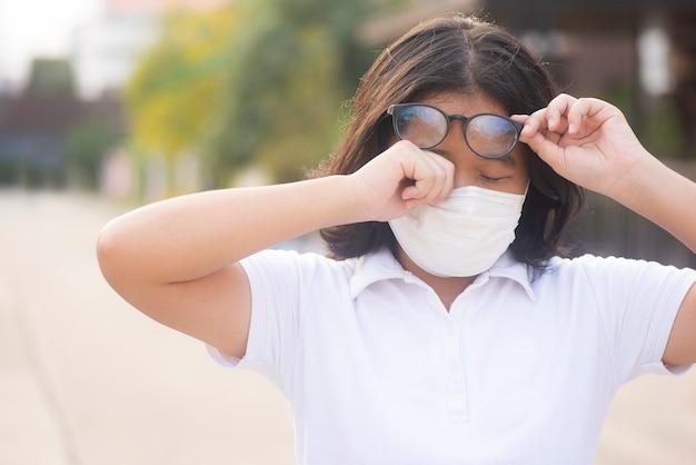 Mulheres asiáticas estão coçando as pálpebras devido à alergia ao ar livre. a mulher está com coceira nos olhos