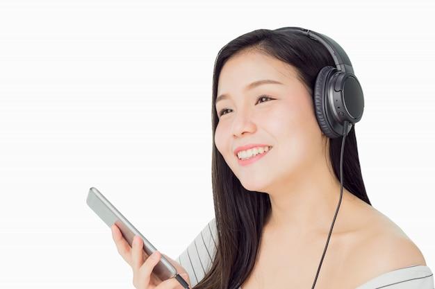 Mulheres asiáticas estão ouvindo música de fones de ouvido pretos. de bom humor e conforto.