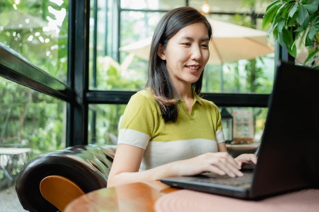 Mulheres asiáticas estão usando seus laptops para trabalhar no café