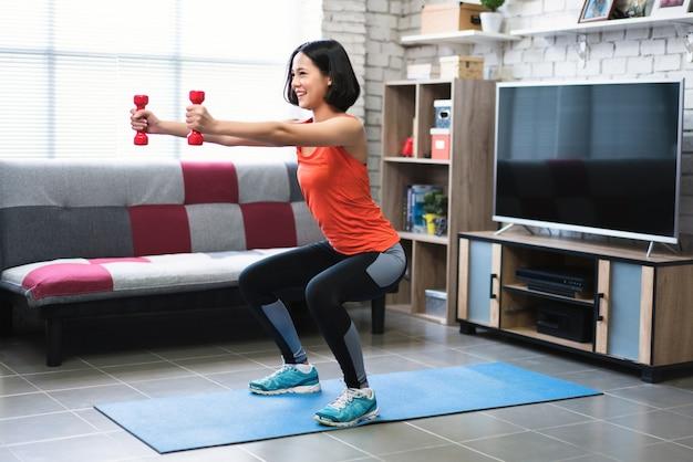 Mulheres asiáticas exercício dentro de casa ela agiu a abóbora em casa