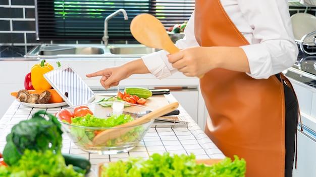Mulheres asiáticas felizes cozinhando comida saudável enquanto procuram uma receita no tablet digital