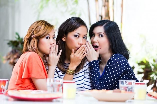 Mulheres asiáticas fofocando sobre coisas