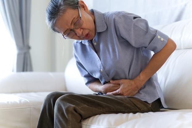 Mulheres asiáticas idosas que têm o problema da dor de estômago.