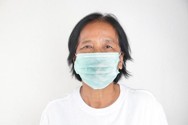Mulheres asiáticas idosas usam máscaras verdes para prevenir o coronavírus (covid-19) e poeira