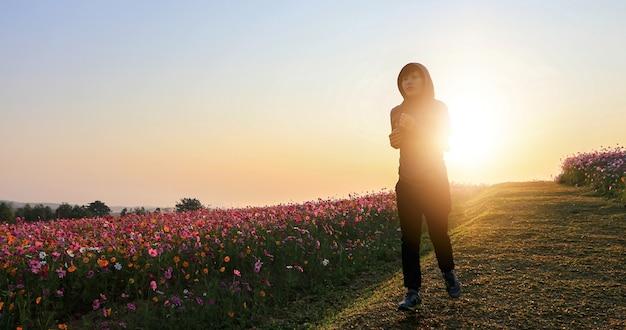Mulheres asiáticas, jogging, ligado, manhã, em, cosmos, flor, campo
