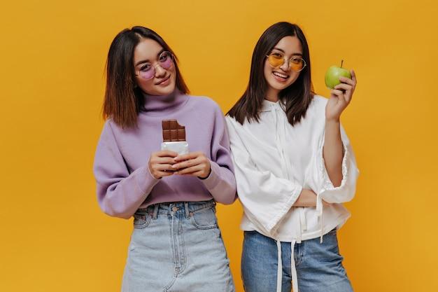 Mulheres asiáticas jovens legais em óculos de sol coloridos olham para frente e sorriem na parede laranja isolada. menina bonita bronzeada com suéter roxo segurando uma barra de chocolate ao leite