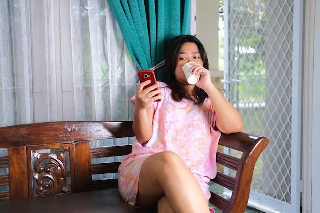 Mulheres asiáticas jovens sentadas, relaxando, desfrutando de uma bebida e jogando no smartphone