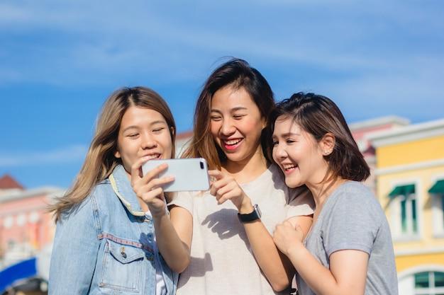 Mulheres asiáticas lindas atraentes amigos usando um smartphone
