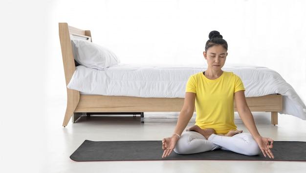 Mulheres asiáticas meditam enquanto pratica ioga