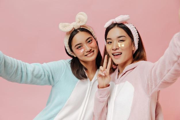 Mulheres asiáticas morenas alegres com kigurumis coloridos e fofos tirando selfie na parede rosa