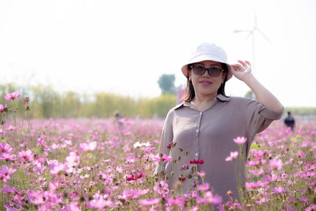 Mulheres asiáticas no campo de flores do cosmos, com fundo de céu claro.