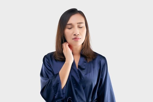 Mulheres asiáticas no robe azul escuro estão coçando o pescoço devido à coceira em um cinza.