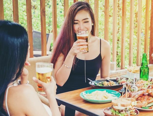 Mulheres asiáticas novas que bebem a cerveja e os vidros do tinido felizes ao apreciar a festa em casa