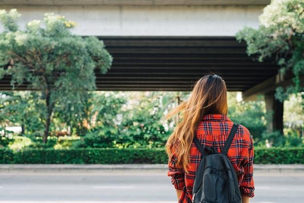 Mulheres asiáticas novas que estão ao longo da rua que aprecia seu estilo de vida da cidade em uma manhã