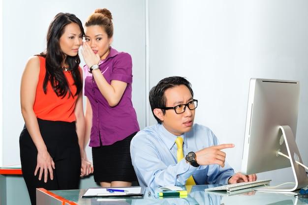 Mulheres asiáticas ou tagarelice de funcionários ou sussurro sobre colega ou homem, intimidando-o no escritório