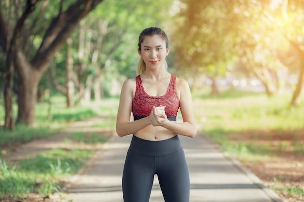 Mulheres asiáticas ouvem música durante um treino no parque.