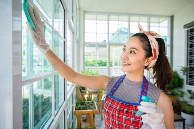 Mulheres asiáticas que desinfetam a porta de vidro e a mesa de limpeza em casa