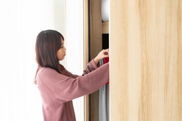 Mulheres asiáticas que escolhem panos em um quarto