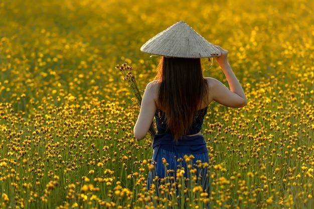Mulheres asiáticas que estão para trás em um campo de flor amarelo bonito.