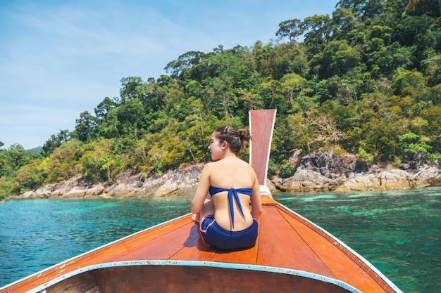 Mulheres asiáticas que relaxam no mar tropical das férias de verão com o barco da longo-cauda em tailândia.