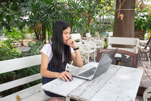 Mulheres asiáticas que trabalham a tarefa com o portátil na tabela de madeira no jardim.