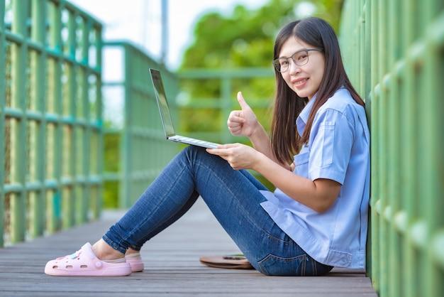 Mulheres asiáticas que trabalham no parque público usando o estilo de vida moderno do laptop