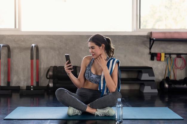 Mulheres asiáticas que usam o smartphone após o exercício no ginásio de fitness. relaxe o estilo de vida.