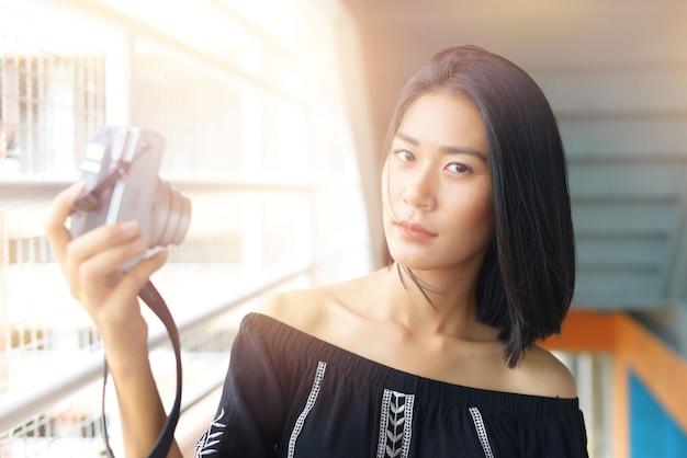 Mulheres asiáticas segurando a câmera tire sua foto ao ar livre.