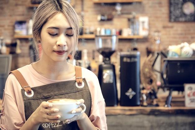 Mulheres asiáticas, segurando a xícara de café no café