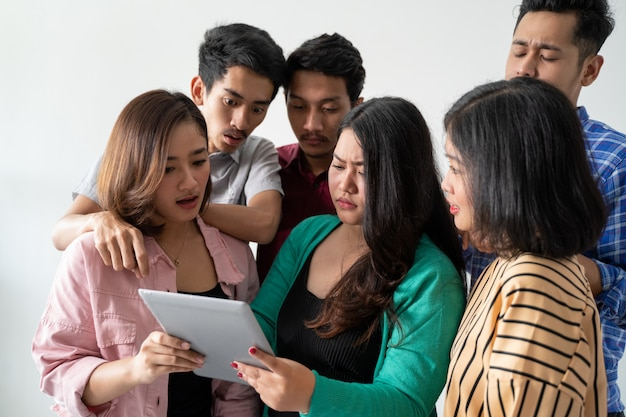 Mulheres asiáticas segurando comprimidos com amigos