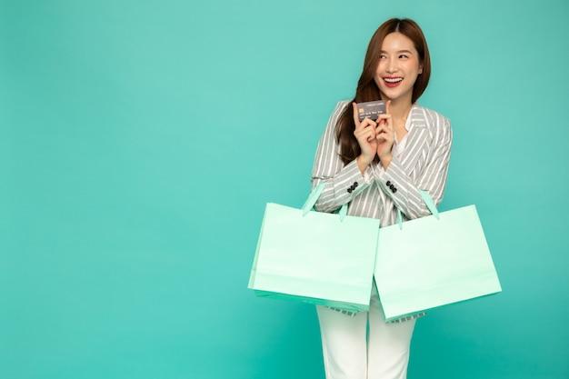Mulheres asiáticas segurando um cartão de crédito e uma sacola de compras verde isoladas sobre fundo verde.