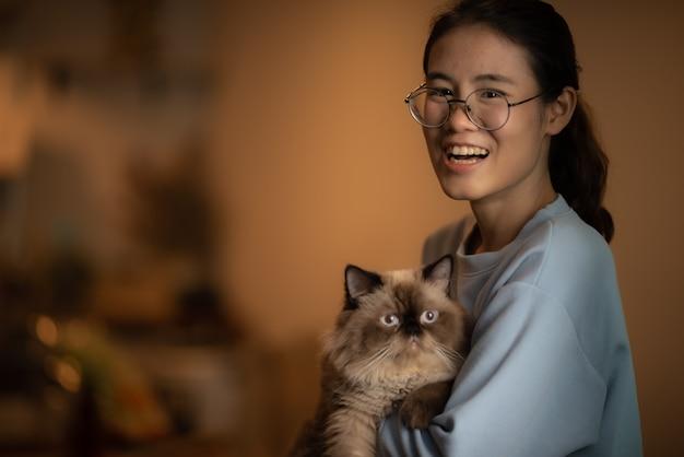 Mulheres asiáticas segurando um gato no braço e sorrindo para a câmera, conceito de estilo de vida, mulheres asiáticas de cabelo preto comprido de óculos, brincando com o gato, amam o conceito de animal de estimação.