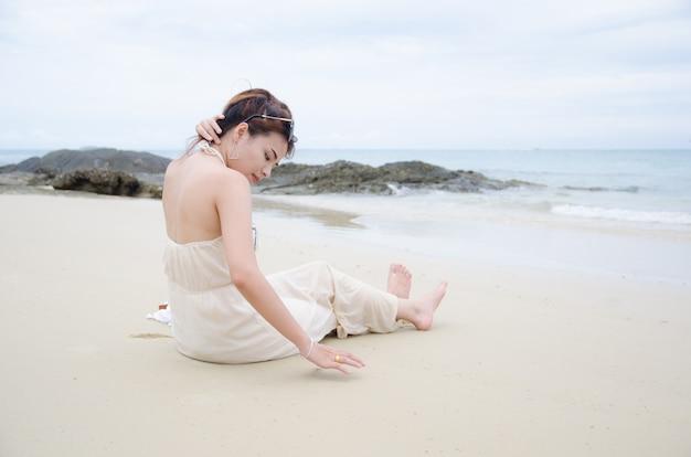 Mulheres asiáticas, sentando, ligado, praia mar, e, toque, dela, cabelo