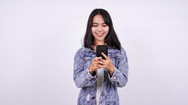 Mulheres asiáticas sorrindo, vestindo jaqueta jeans e segurando um telefone com uma superfície branca isolada