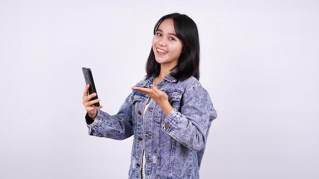 Mulheres asiáticas sorrindo, vestindo jaqueta jeans, segurando e apontando para o telefone com uma superfície branca isolada