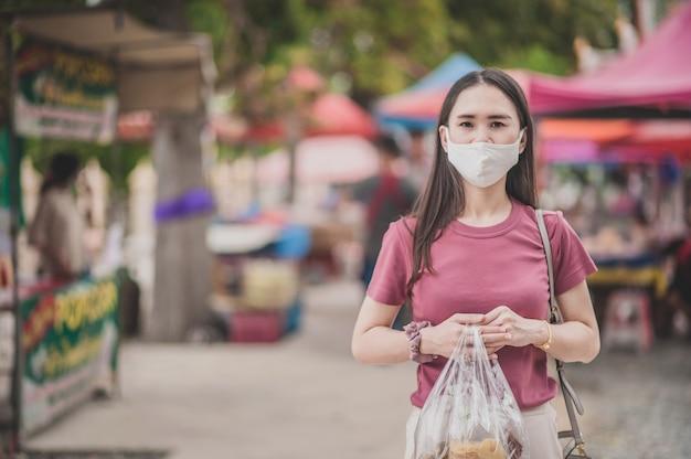 Mulheres asiáticas tailandesas usam máscara facial de compras no mercado de rua novo elevador normal depois que o vírus corona é desbloqueado