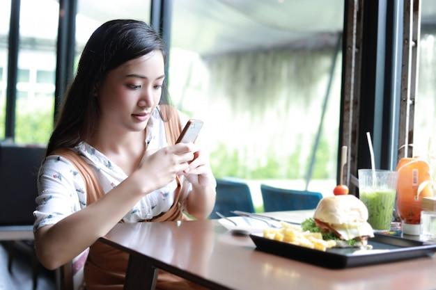 Mulheres asiáticas tirando foto de hambúrgueres e gostava de comer no café e restaurante na hora de relaxar