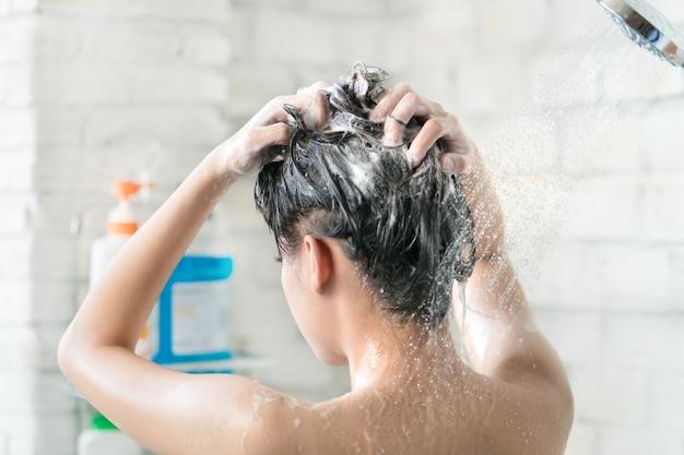 Mulheres asiáticas tomando banho e ela estava tomando banho e lavando cabelo. ela está feliz