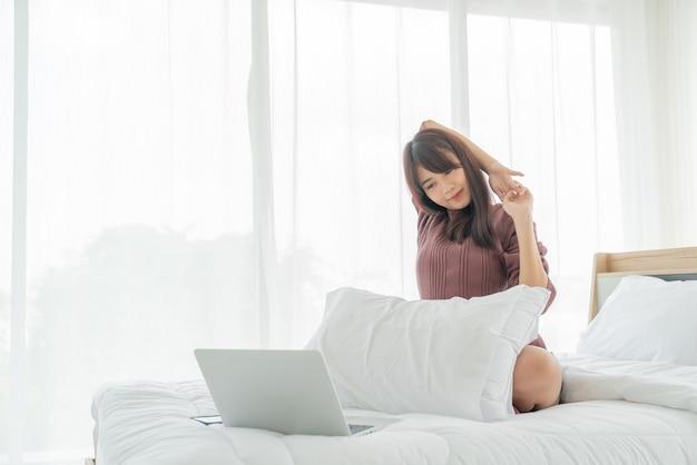 Mulheres asiáticas trabalhando com laptop na cama em casa
