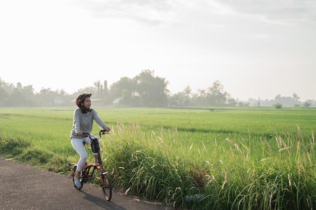 Mulheres asiáticas usam capacetes para andar de bicicleta dobrável nos campos de arroz