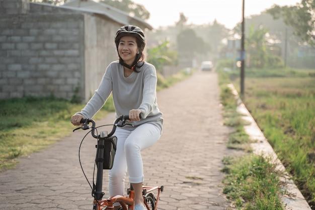 Mulheres asiáticas usam capacetes para andar de bicicleta dobrável