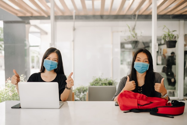 Mulheres asiáticas usando máscaras no escritório Foto Premium