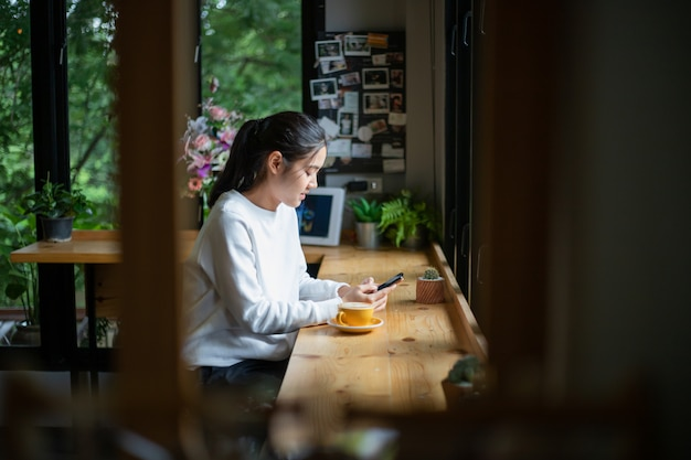 Mulheres asiáticas, usando mensagens de escrita em um telefone celular na loja de café