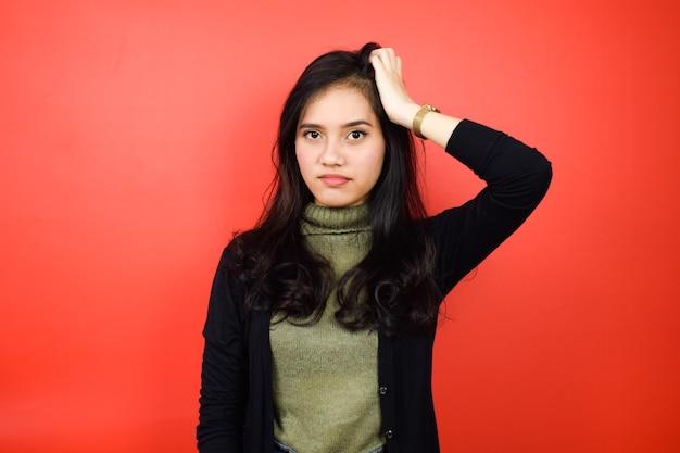 Mulheres asiáticas usando suéter preto tocando sua cabeça e confuso com fundo vermelho isolado