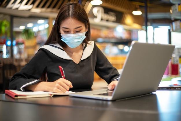 Mulheres asiáticas usando uma máscara e ela trabalhando e estudando online com seus notebooks.