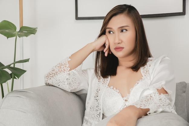 Mulheres asiáticas vestindo pijamas de cetim branco sentadas em um sofá cinza e olhando de lado mulher distraída