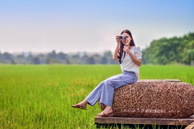 Mulheres asiáticas viajam na natureza com câmera tirando foto