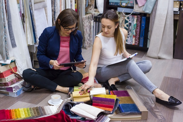 Mulheres assistem amostras de tecidos para cortinas