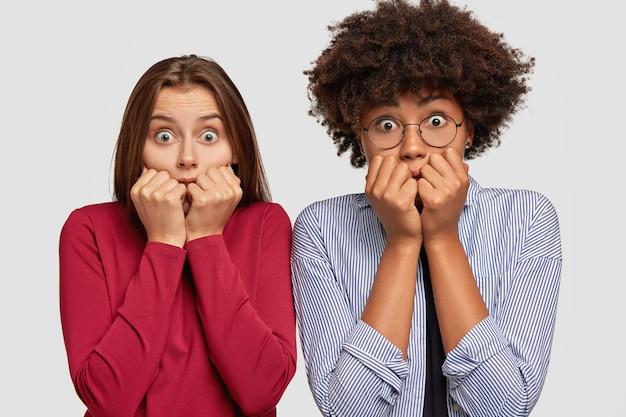 Mulheres assustadas parecem ansiosas, roem as unhas e olham com olhos arregalados
