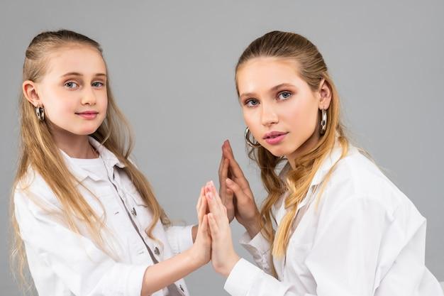 Mulheres atraentes de cabelos compridos, olhos azuis e roupas brancas de mãos dadas